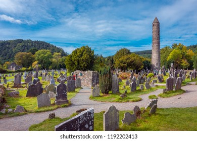 Stone round tower and some ruins of a monastic settlement originally built in the 6th century in Glendalough valley, County Wicklow, Ireland