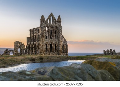 Stone ruins of Whitby Abbey on the cliffs of Whitby, North Yorkshire, England at sunset.