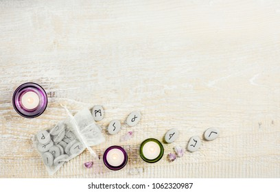 Stone runes on the light wooden background. Magical items concept.