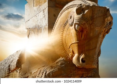Stone sculpture of a horse in Persepolis against a sunrise. Iran. Persia. Shiraz. Rays of lights.