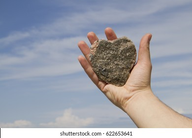 Stone in the shape of a heart held in a man's hand with sky background