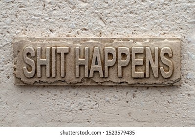 Stone slab on a wall with lettering: Shit happens