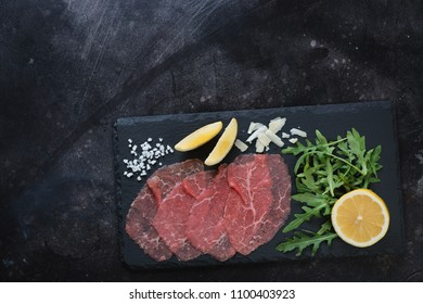 Stone slate with carpaccio beef, arugula, lemon and parmesan. View from above on a dark scratched metal background with space