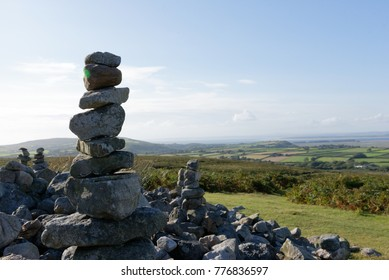 Stone stacks or cairns with blue sky and cloud background near Arthur's Stone, Gower, Swansea, Wales, UK