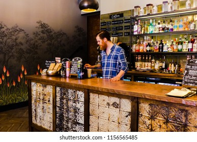 Stone, Staffordshire. England - August 13, 2018 : Interior of Ten Green Bottles, an upmarket bar. Looking towards the counter with bartender. Drinks bottles & signage in background. Mural & lighting.