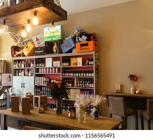 Stone, Staffordshire. England - August 13, 2018 : Interior of Ten Green Bottles, an upmarket bar. Looking towards empty customer tables. Drinks bottles & signage in background. Lighting and staging.
