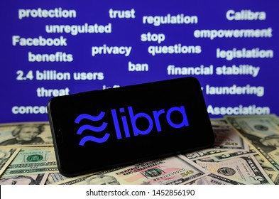 Stone, Staffordshire /UK - July 16 2019:  Smartphone with Libra logo placed on dollar bills. And a background filled with keywords form Senate Banking Committee hearing on Facebook's Libra currency.