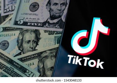Stone, Staffordshire / UK - October 27, 2019: TikTok app logo on the smartphone screen and US dollar bills next to it. Top down view. Conceptual photo.