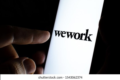 Stone, Staffordshire / UK - October 27, 2019: WeWork company logo on the smartphone screen in a dark room and a finger pointing at it.  WeWork provides the office space and workspace solutions.