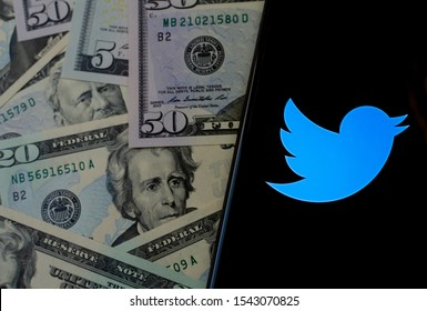 Stone, Staffordshire / UK - October 27, 2019: Twitter logo on the smartphone screen and US dollar bills next to it. Top down view. Conceptual photo.