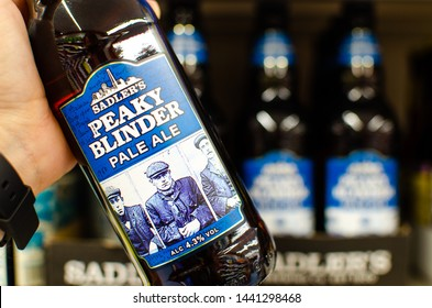Stone, Staffordshire / United Kingdom - July 3 2019: Peaky Blinder Pale Ale bottle in the hand with a multiple bottles at the background.