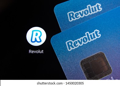 Stone, Staffordshire / United Kingdom - July 13 2019: Revolut bank cards on the smartphone screen next to app icon.  Revolut Ltd is a UK financial technology company that offers banking services.