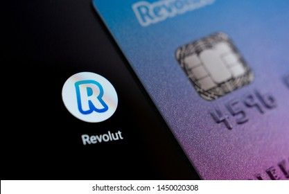 Stone, Staffordshire / United Kingdom - July 13 2019: Revolut bank card on the smartphone screen next to app icon.  Revolut Ltd is a UK financial technology company that offers banking services.