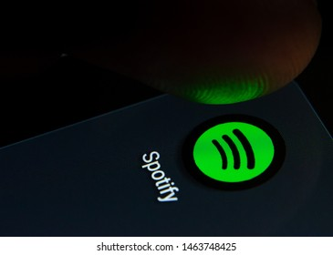 Stone, Staffordshire / United Kingdom - July 28 2019: Spotify app icon on the smartphone screen with visible pixels and the finger about to launch it. Extreme close up photo.