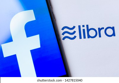 Stone, Staffordshire / United Kingdom - June 18 2019: Photo of Facebook logo on the smartphone screen and the brochure with Libra logo. Illustrative for news on Libra cryptocurrency announcement.