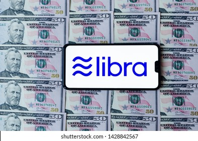 Stone, Staffordshire / United Kingdom - June 19 2019: Facebook Libra logo on smartphone that put on 50 dollar banknotes. Conceptual photo points out the similarity of symbols on bills and Libra logo.