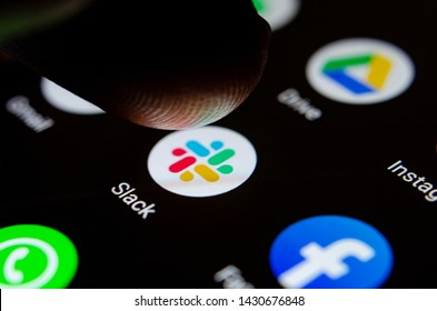 Stone, Staffordshire / United Kingdom - June 21 2019: Close up photo Slack app on the smartphone screen and a finger launching it. The top app for communication and collaboration.