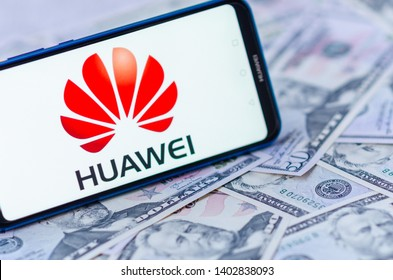 Stone, Staffordshire / United Kingdom -May 20, 2019: The close up photo of mobile phone on the dollar bills with HUAWEI logo on the screen. The conceptual editorial photo shows US-China tensions.