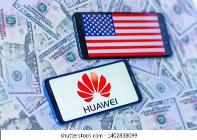 Stone, Staffordshire / United Kingdom -May 20, 2019: The close up photo of two mobile phones on dollars with Chinese HUAWEI logo and American flag. The conceptual editor photo shows US-China tensions.