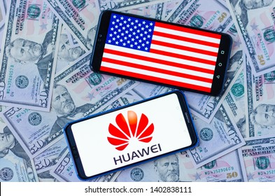 Stone, Staffordshire / United Kingdom -May 20, 2019: The close up photo of two mobile phones on dollars with HUAWEI logo and American flag. The conceptual editorial photo shows US-China tensions.