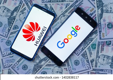 Stone, Staffordshire / United Kingdom -May 20, 2019: The close up photo of two mobile phones on dollars with Chinese HUAWEI and Google logos. The conceptual editorial photo shows US-China tensions.