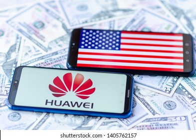 Stone, Staffordshire / United Kingdom -May 23, 2019: The close up photo of mobile phones on dollars with Chinese HUAWEI logo and flag America. The conceptual editorial photo shows USA China tensions.
