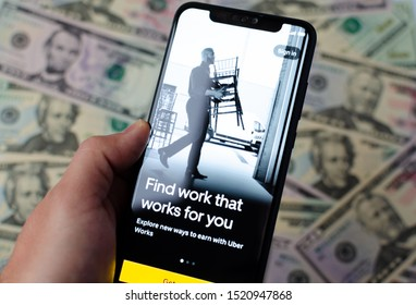 Stone, Staffordshire / United Kingdom - October 3 2019: Uber Works app start screen on the smartphone and dollar bills on background. Uber is entering a labour market. Photo with selective focus.