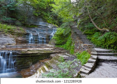 A stone stair follows a series of cascades.  Summer within the gorge of Buttermilk Falls Park.