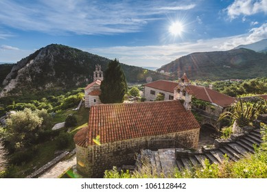 Stone staircase, chapel and traditional serbian church with bell tower at Gradiste monastery near Buljarica, Montenegro. Mountains, churchyard and abbey under evening lights .