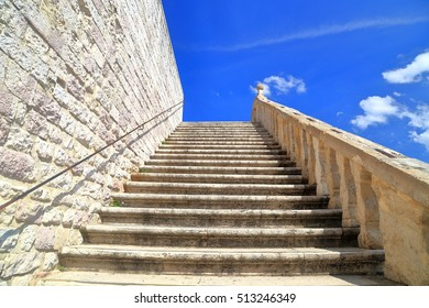Stone stairs ascending towards blue sky at the Basilica of San Francesco in Assisi, Umbria, Italy
