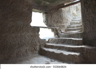 Stone stairs to the basement with a window cut in the rock