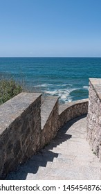 stone stairs leading down to the beach with view of the ocean on a sunny summer day. Taken in Praia Das Macas in Portugal