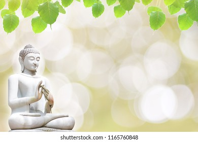 Stone statue of Buddha and bodhi leaf on bokeh background. Religion background, buddhism background.