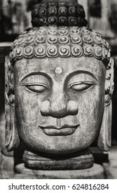 Stone statue of calm japanese Buddha textured in grey tones with scratches and stains for a worn look.