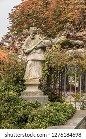 Stone statue with colored leaves of a tree and ivy