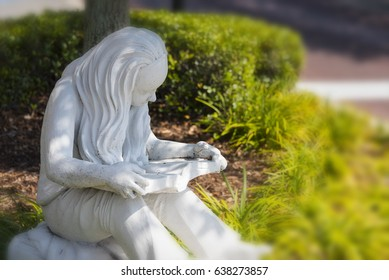 Stone statue of a girl with long hair reading a book in the grass near a tree