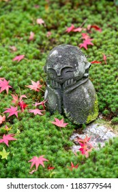 Stone statue of Jizo on ground covered by green star moss and red maple leaves at Enkoji temple, Kyoto Japan