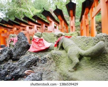 Stone statue and Senbon Torii at Fushimi Inari Shrine (Japan: Kyoto). Torii is the gate of a shrine. It is written as Votive in the torii.