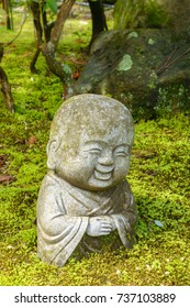 stone statue of smiling Buddha surrounded by moss