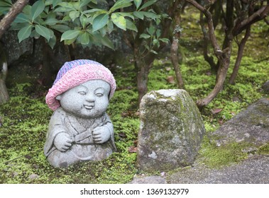 Stone statue of smiling Jizo (Jizo Bosatsu) in a knitted hat, Miyajima, Japan