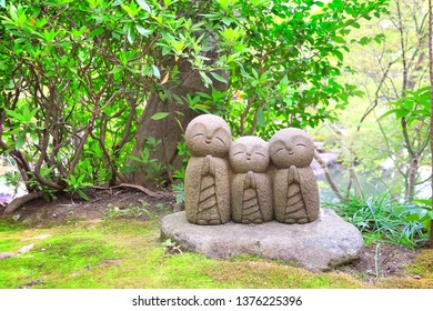 Stone statue of three smiling Jizo (Jizo Bosatsu), Hasedera temple, Kamakura, Japan