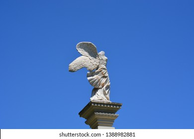Stone statue of the winged goddess Nike on blue sky background