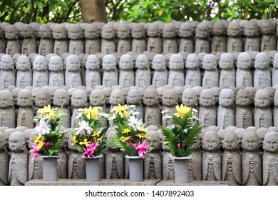 Stone statues of Ksitigarbha (Jizo Bosatsu), Hasedera (Hase-dera) temple, Kamakura, Japan. Focus on flowers