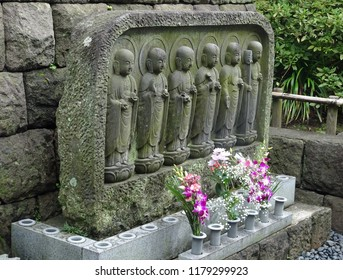 Stone statues of little bald men (known as Jizo) with bunches of flowers at a shrine in Japan