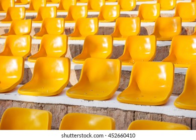 Stone steps with yellow plastic seats. Empty stools without people. Concept photo - absence of audience.