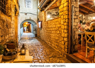 Stone street in the old town of Trogir, Croatia. Night scene with traditional restaurant. Travel destination.