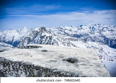 A stone tabletop with space for your product or advertising text. View of winter alpine mountains. Beautiful December sky in blue color.