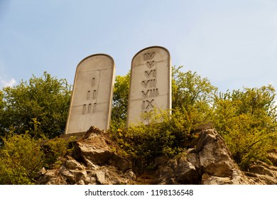 Stone tablets on a rocky hill with carved 10 commandments
