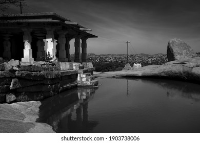 Stone temple next to a pond overlooking a valley with boulders close by, in Hampi, Karnataka, India