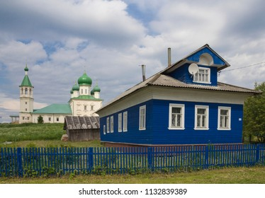 Stone temple and wooden house. Russia, Lomonosovo village, Arkhangelsk region